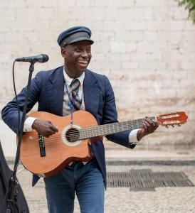 un artiste de rue joue de la guitare dans les rues de lisbonne