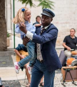 Un artiste de rue fait danser une petite fille